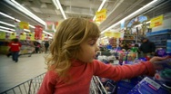 Stock Video Footage of little girl sitting in shopping trolley buying toys in mall