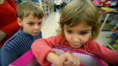 Little girl and boy playing logic game in mall Stock Footage