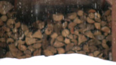Snow storm falling in a winter forest woodpile defocused storm blizzard weather Stock Footage