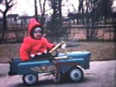 Stock Video Footage of Little Boy Rides Car Outside (1964 - Vintage 8mm film)