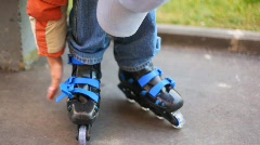 Boy puts on roller skates Stock Footage