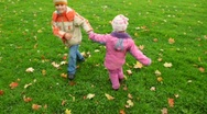 Boy and little girl spinning in autumn park, join hands Stock Footage