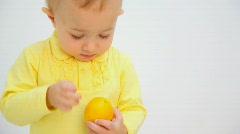 Little boy peeling orange against white background Stock Footage