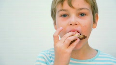 Boy eating sandwich against white background Stock Footage