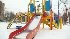 Little girl playing on slide in deep snow city playground, winter Stock Footage