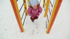 Little girl teetering in deep snow city playground, winter Stock Footage