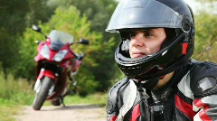 Biker sits near motorcycle, see and close visor on it helmet Stock Footage