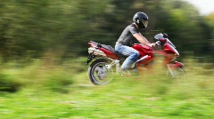 Motorcyclists on red bike crosses park Stock Footage