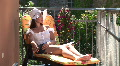 HD1080i Young brunette sexy woman with sunglasses and white hut on balcony. Footage