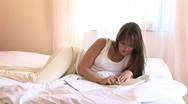 HD1080i Young sexy brunnete woman in underwear lie on a bed and read a book Stock Footage