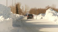 Cars driving through cleared street after snow storm, #3 long shot Stock Footage