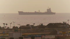 Anchored cargo ship, construction in foreground Stock Footage