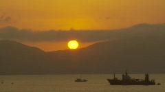 Sun setting behind mountaisn and ships in bay Stock Footage