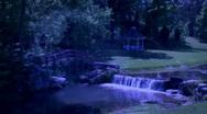 Gazebo near Waterfall Waterwheel Bridge River at night Stock Footage