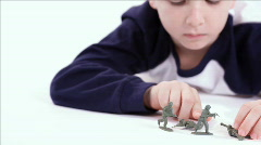 Dolly right boy playing with toy soldiers Stock Footage