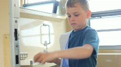 Boy with towel brushing teeth in bathroom of carriage Stock Footage