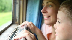 Young woman and boy looking at nature from moving railway carriage Stock Footage