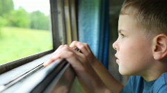 Boy looking at nature from moving railway carriage Stock Footage