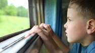 Stock Video Footage of boy looking at nature from moving railway carriage