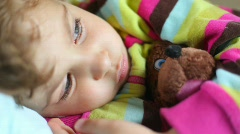 Cute sleepy little girl with toy bear lying in bed and blinking Stock Footage