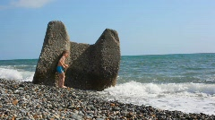 Young boy hiding behind boulder in beach from sea surf Stock Footage