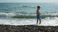 Boy standing in sea surf and throwing pebbles to water Stock Footage
