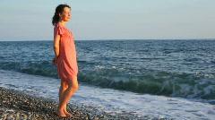 Young beautiful woman standing in pebble beach near waving sea Stock Footage