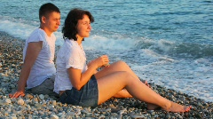 Young woman and man sitting in pebble beach near sea Stock Footage