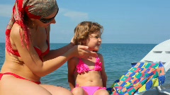 Mother spreading tanner on her little daughter in pebble beach Stock Footage