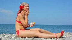 Young woman dressed in swimsuit spreading tanner on her face Stock Footage