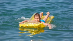 Young boy oaring on yellow inflatable mattress in sea Stock Footage