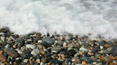 Sea surf with spume covering pebble coast, macro shooting Stock Footage