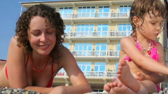 Woman and little girl fingering stones in pebble beach, hotel in background Stock Footage