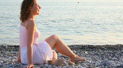Young smiling woman sitting on pebble beach, sea in background Stock Footage