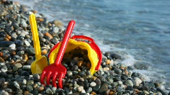 Yellow children's bucket with scoop on pebble seacoast Stock Footage