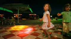 Two cute little girls dancing in night club Stock Footage