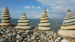 Pebble stack on the stone seashore, sea and sky in background Stock Footage