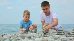 Father with son building stone stacks on pebble beach, sea Stock Footage