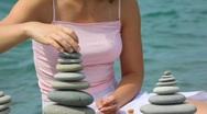 Headless woman building stone stack on pebble beach, sea Stock Footage