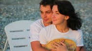 Stock Video Footage of embracing smiling young couple sitting on beach in sunset light
