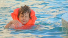 Little girl dressed in orange inflatable waistcoat swimming in pool Stock Footage