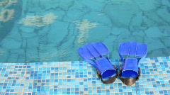 Blue flippers is on mosaic edge of swimming pool with clear water Stock Footage