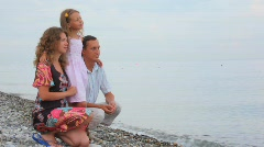 Family of three persons sitting on pebble coast and looks at sea Stock Footage