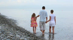 Family of three persons walking in sea surf, join hands, from camera Stock Footage