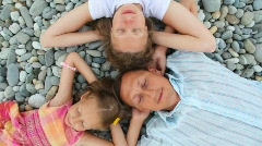 Happy family of three persons lying on pebble beach, top view Stock Footage