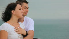 Standing in beach young couple looks at sea, hairs swaying by wind Stock Footage