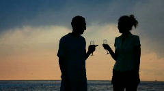 Silhouettes of man woman with goblets drinking champagne and kissing Stock Footage