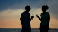 Stock Video Footage of silhouettes of man woman with goblets drinking champagne and kissing