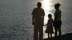 Silhouettes of family standing in beach and looking at sea Stock Footage