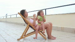 Young woman sitting on chair outdoor and combing hair her little daughter Stock Footage